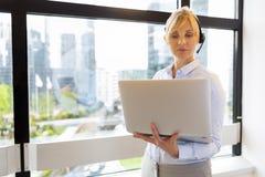 有吸引力的企业膝上型计算机妇女工作 耳机 背景大厦商务中心墙壁视窗 图库摄影