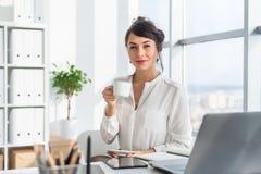 年轻有吸引力的办公室工作者水杯茶,有咖啡休息在早晨,准备好在工作天 库存图片