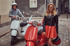 有吸引力的夫妇、一个英俊的人和性感的女性身分在一条老街道上有两辆减速火箭的滑行车的 免版税库存图片