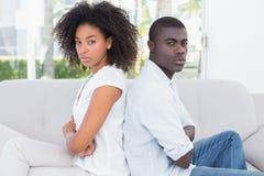 有吸引力的夫妇不谈话在长沙发 库存图片