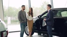 有吸引力的夫妇与汽车销售主任在豪华售车行中谈话并且看美丽的黑汽车 股票录像