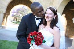 有吸引力的夫妇人种间亲吻的婚礼 免版税库存照片