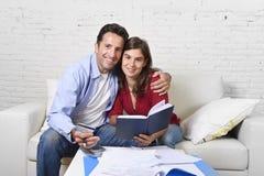 有吸引力的夫妇会计债务在家长沙发愉快在财政成功和财富 免版税库存照片