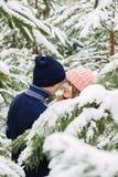 有吸引力的夫妇在冷杉木中的冬天森林里 免版税图库摄影