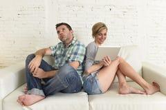 有吸引力的夫妇在家横卧数字式片剂的愉快的妇女互联网上瘾者忽略哀伤的丈夫的 免版税库存图片