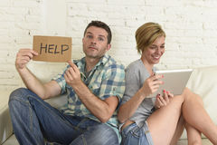 有吸引力的夫妇在家横卧数字式片剂的愉快的妇女互联网上瘾者忽略哀伤的丈夫的 库存图片