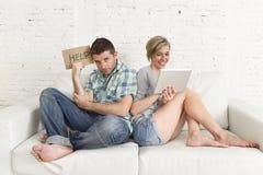 有吸引力的夫妇在家横卧数字式片剂的愉快的妇女互联网上瘾者忽略哀伤的丈夫的 库存照片