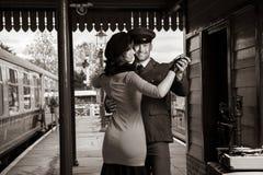有吸引力的夫妇在有便携式的电唱机的火车站平台跳舞 免版税库存照片