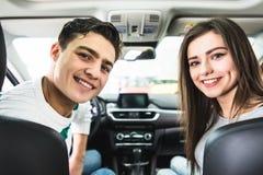 有吸引力的夫妇在陈列室里选择一辆新的汽车,坐在汽车 从汽车的后面看法 免版税库存照片