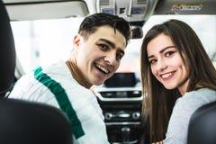 有吸引力的夫妇在陈列室里选择一辆新的汽车,坐在汽车 图库摄影