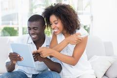 有吸引力的夫妇坐一起看片剂的长沙发 免版税库存照片