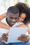 有吸引力的夫妇坐一起看片剂的长沙发 库存图片