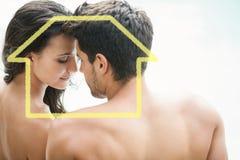 有吸引力的夫妇坐的游泳池边微笑的综合图象 图库摄影