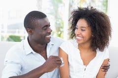 有吸引力的夫妇坐结合在一起使信用卡的长沙发 库存照片