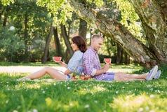有吸引力的夫妇有一顿浪漫野餐在公园 免版税库存图片