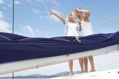 有吸引力的夫妇站立在帆船的-航行旅行。 库存照片