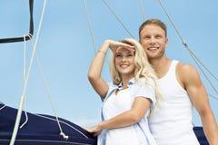 有吸引力的夫妇站立在帆船的-航行旅行。 库存图片