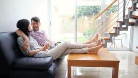 有吸引力的夫妇谈的坐长沙发在现代家 股票录像