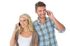 有吸引力的夫妇谈话在他们的智能手机 库存照片