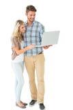 有吸引力的夫妇身分和使用膝上型计算机 免版税库存图片