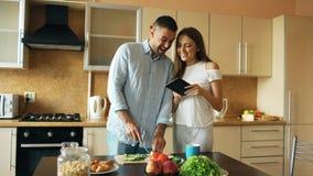 有吸引力的夫妇集会在厨房清早 使用片剂的英俊的妇女分享他的丈夫社交媒介 免版税库存图片