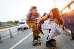 年轻有吸引力的夫妇骑马踩滑板和获得乐趣 库存图片