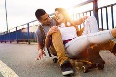 年轻有吸引力的夫妇骑马踩滑板和获得乐趣 免版税图库摄影
