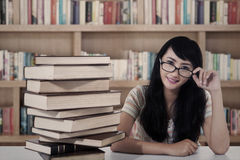 有吸引力的女学生和书在图书馆 免版税库存图片