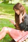 有吸引力的女孩公园电话 免版税库存照片