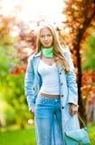 有吸引力的女孩牛仔裤室外摆在 免版税库存图片