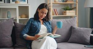 有吸引力的女孩看书藏品咖啡的慢动作在家 影视素材