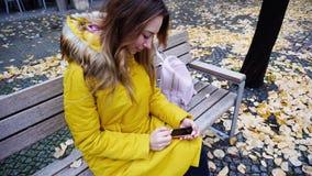 有吸引力的女性举行的智能手机和浏览照片, sittin 图库摄影