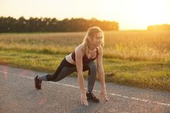 有吸引力的女性佩带的体育鞋子和衣裳,做体育在路行使反对日落,喜欢体操,舒展她 库存图片