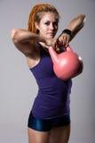 年轻有吸引力的女性做的水壶响铃锻炼o画象  图库摄影