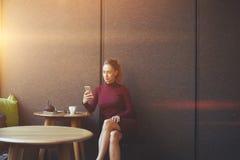 有吸引力的女性观看的录影或读在网络的企业weblog在手机 免版税库存照片