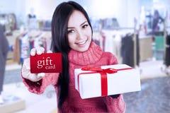 有吸引力的女性顾客展示礼品券和箱子 免版税库存图片