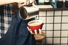 有吸引力的女性barista的播种的图象拿着杯子拿铁在一家斯堪的纳维亚式咖啡店 库存照片