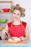 有吸引力的妇女剪切面包在厨房里 库存照片