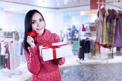 有吸引力的妇女展示礼品券和礼物在商城 库存照片