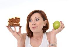 有吸引力的妇女点心挑选破烂物蛋糕或苹果计算机 免版税库存图片