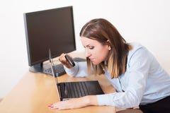 有吸引力的妇女用途她的工作的一个放大镜在办公室 图库摄影