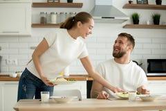 有吸引力的妻子服务食物为丈夫烹调了在厨房里 库存照片