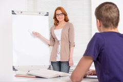 年轻有吸引力的家庭教师女孩教学 库存图片
