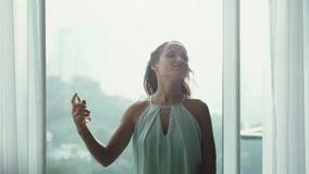 有吸引力的少女晨衣与城市视图盆射在pnoramic窗口背景的香水芬芳和 影视素材