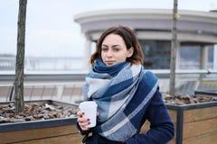 有吸引力的少妇佩带的围巾和拿着加奶咖啡杯子画象在一个冷和多雪的冬日 库存照片