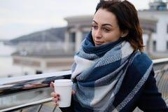 有吸引力的少妇佩带的围巾和拿着加奶咖啡杯子画象在一个冷和多雪的冬日 免版税图库摄影
