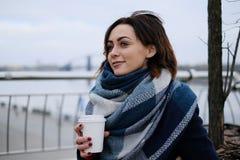 有吸引力的少妇佩带的围巾和拿着加奶咖啡杯子画象在一个冷和多雪的冬日 库存图片