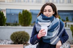 有吸引力的少妇佩带的围巾和拿着加奶咖啡杯子画象在一个冷和多雪的冬日 免版税库存照片
