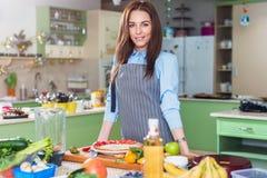 有吸引力的年轻人画象烹调摆在站立的佩带的围裙在工作场所用新鲜的水果和蔬菜在桌上 库存照片