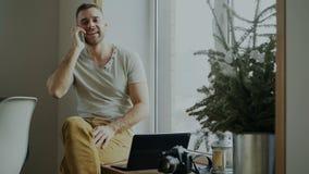 有吸引力的年轻人谈的电话在家坐与膝上型计算机和照相机的窗台 影视素材